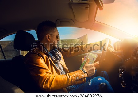 Fashion model male driving car with lot of money in hand. Inside photo - stock photo