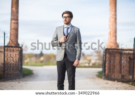 Fashion model man posing in autumn park. Smart casual outfit. - stock photo