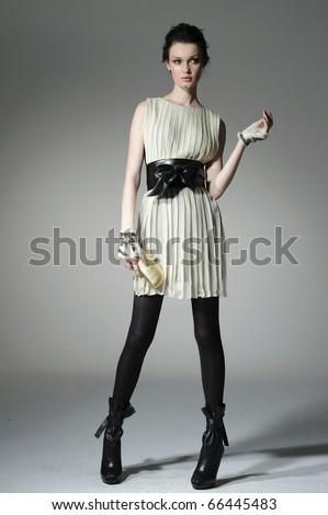 fashion model model holding little purse on gray background - stock photo