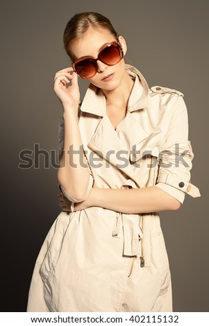 Fashion model posing at studio in a coat and sunglasses. Beauty, fashion. Business style. - stock photo