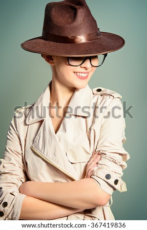 Fashion model posing at studio in a coat, hat and spectacles. Beauty, fashion. Business style. - stock photo