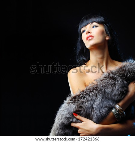 Fashion model posing at studio wearing fur and looking at copy space  - stock photo