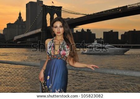Fashion model posing in long blue dress in front of Brooklyn Bridge in New York City - stock photo
