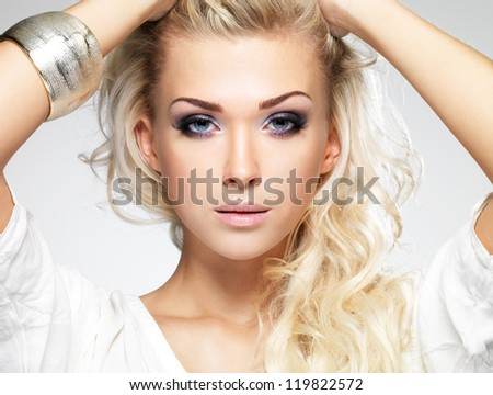 Fashion model posing in studio. Portrait of a beautiful blond woman with saturated makeup. Girl posing on white background - stock photo