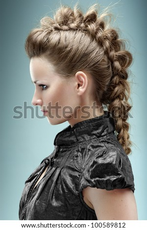 Fashion model posing  in the studio with hairstyle in a black short blouse. Hairdressing. - stock photo