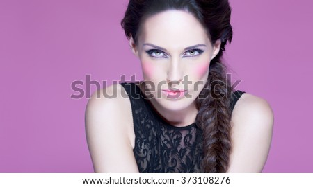 Fashion model posing over pink purple background with intense makeup. Fashion and beauty concept.  - stock photo
