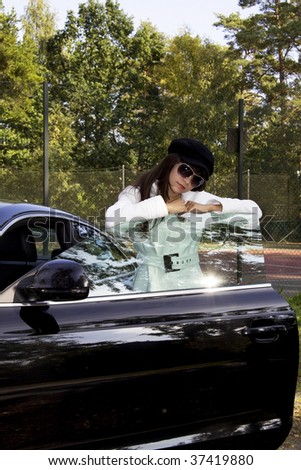 Fashion model wearing a white coat and a black beret hat standing outside a luxury car