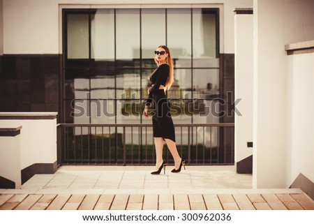 fashion model wearing sunglasses in the city. copy space. walking near the shopping center