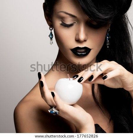 Fashion model with black nails and style makeup holds the white apple - stock photo