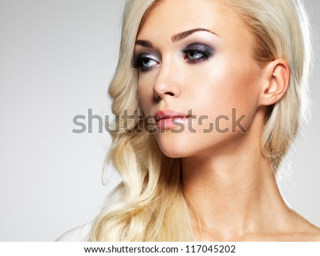Fashion model with bright make-up. Portrait of young fashion woman with long blond hair - stock photo