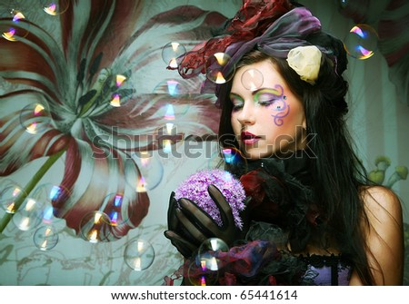 fashion model with creative make-up blowing soap bubbles. Doll style. - stock photo