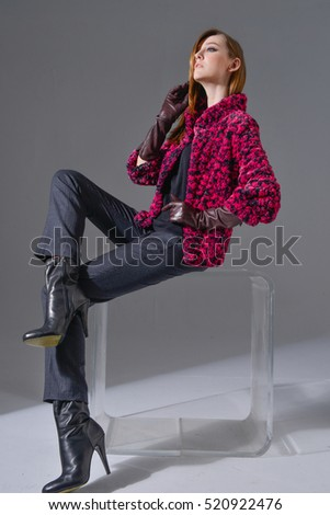 fashion model with gloves, boots sitting cube in studio