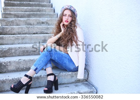 fashion model with long curly hair wearing sunglasses posing outdoor. Jeans, shoes, hat, jacket.