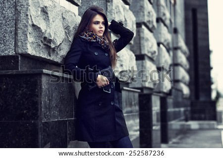Fashion model with sunglasses, black coat, scarf, and handbag clutch. Outdoor shot - stock photo