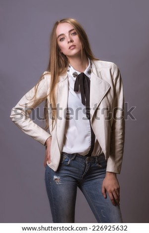 Fashion model woman in white leather coat and jeans - stock photo