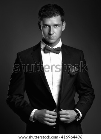 fashion monochrome portrait Handsome man in suit. young groom man with flower.elegant boy - stock photo