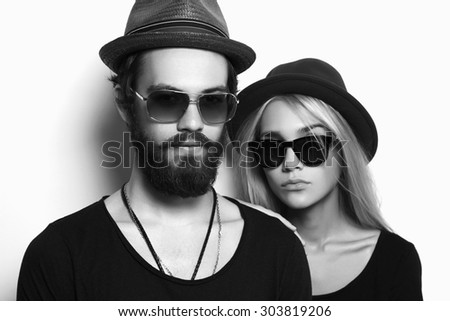 fashion monochrome portrait of beautiful couple together. Hipster boy and girl. Bearded young man and blonde in sunglasses - stock photo