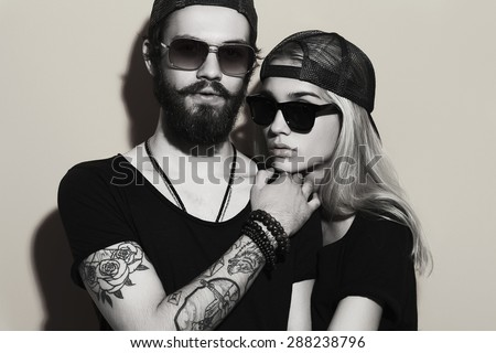 fashion monochrome portrait of beautiful couple together. Tattoo Hipster boy and girl. Bearded young man and blonde in sunglasses - stock photo