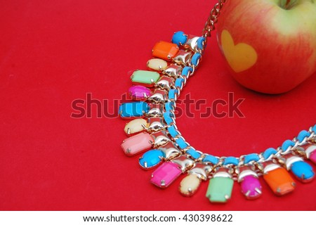 Fashion necklace and love apple on red background