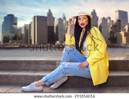 Fashion outdoor photo of beautiful luxury woman wearing hat, yellow jacket and blue jeans sitting on stair. City background. Summer fashion concept