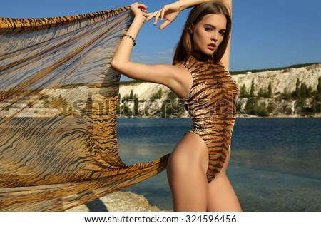 fashion outdoor photo of beautiful model with dark hair wears elegant leopard print suit, posing beside a lake  - stock photo
