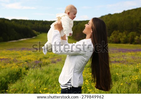 fashion outdoor photo of beautiful mother posing with her cute little baby in blossom spring garden