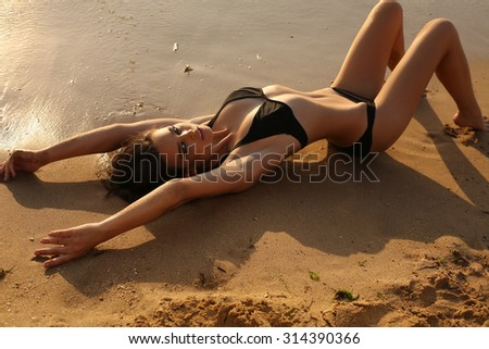 fashion outdoor photo of beautiful sexy girl with dark hair and tanned skin wears black bikini relaxing on summer beach