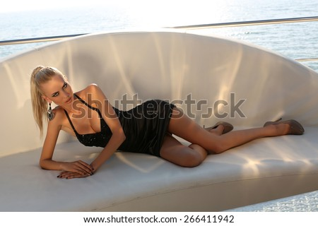 fashion outdoor photo of beautiful sexy woman with long blond hair wearing elegant black dress,lying on white leather divan - stock photo