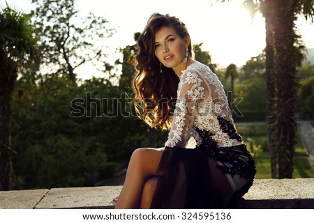 fashion outdoor photo of beautiful woman with dark hair wears luxurious dress,posing in summer park  - stock photo