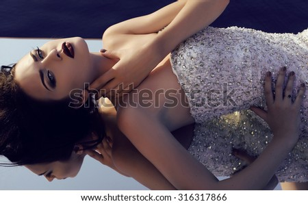 fashion outdoor photo of beautiful young woman with dark hair in luxurious sequin dress lying on mirror  - stock photo
