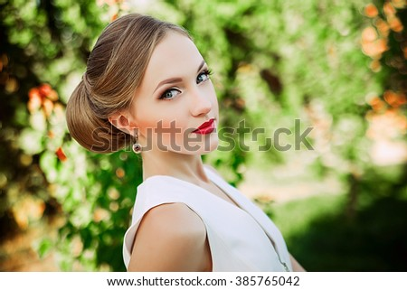 fashion outdoor photo of gorgeous sensual woman with luxurious hairstyle in elegant white cloth posing in blossom garden - stock photo