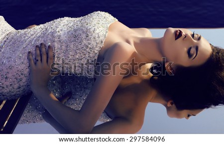 fashion outdoor photo of gorgeous woman with dark hair and bright makeup wearing luxurious sequin dress lying on the mirror - stock photo