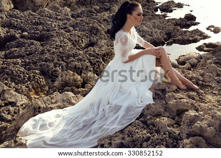 fashion outdoor photo of gorgeous young woman with long dark hair in luxurious lace wedding dress,dreaming on the sea coast - stock photo