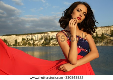 fashion outdoor photo of gorgeous young woman with short dark hair wears luxurious red dress,posing on summer beach - stock photo