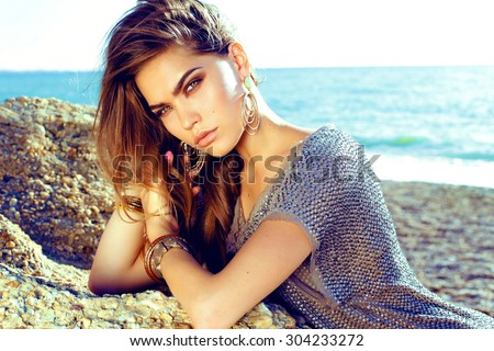 Fashion outdoor photo of sexy beautiful elegant woman with long hair dressed in a luxurious evening dress posing on the summer beach next to the blue ocean - stock photo