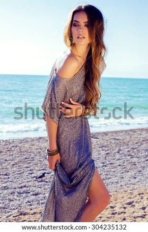 Fashion outdoor photo of sexy beautiful elegant woman with long hair dressed in a luxurious evening dress posing on the summer beach next to the sea - stock photo