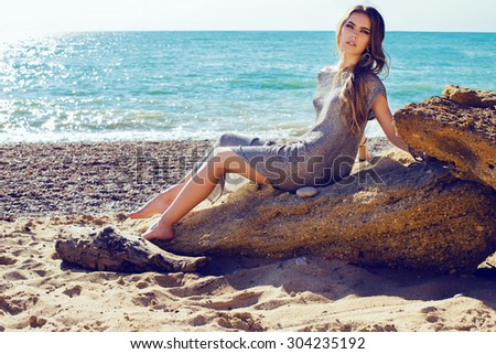 Fashion outdoor photo of sexy beautiful elegant woman with long hair dressed in a luxurious evening dress resting on the summer beach next to the turquoise sea - stock photo