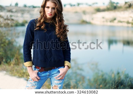 Fashion outdoor photo of sexy beautiful woman with dark curly hair and slim sexy body wearing a knit blue pullover with jeans and posing  against the backdrop of the lake - stock photo