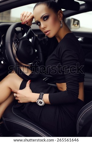 fashion outdoor photo of sexy beautiful woman with dark hair in black elegant dress posing in luxurious auto - stock photo