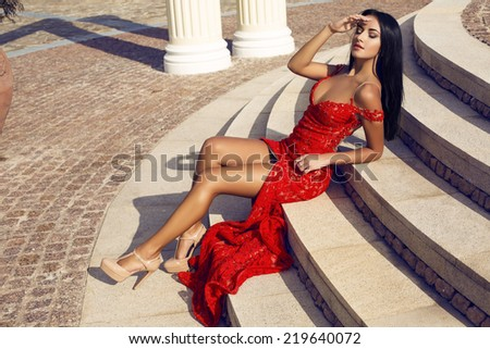 fashion outdoor photo of sexy beautiful woman with dark hair in luxurious elegant dress posing on stairs in park