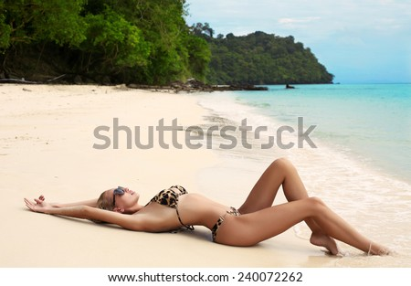 fashion outdoor photo of sexy beautiful woman with long blond hair wearing elegant bikini and sunglasses relaxing on beach ,enjoying her vacation on island   - stock photo