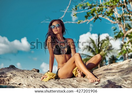 fashion outdoor photo of sexy beautiful woman with long hair in elegant black bikini with accessories relaxing on summer beach - stock photo