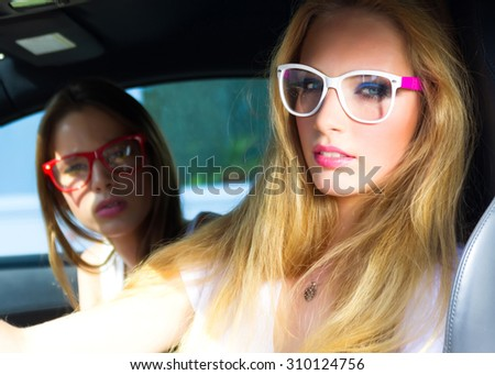 Fashion outdoor portrait of beautiful woman with blonde hair in white t-shirt and  clear sunglasses sitting on driver seat in luxurious auto.Hipster Women driving Car On Road Trip. - stock photo