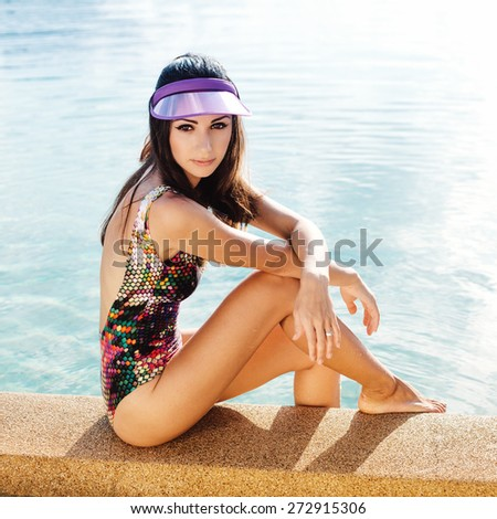 Fashion outdoor portrait of pretty sexy brunette tanned woman having fun in summer on tropic island close to swimming pool with clear deep blue water. Outdoors lifestyle portrait - stock photo