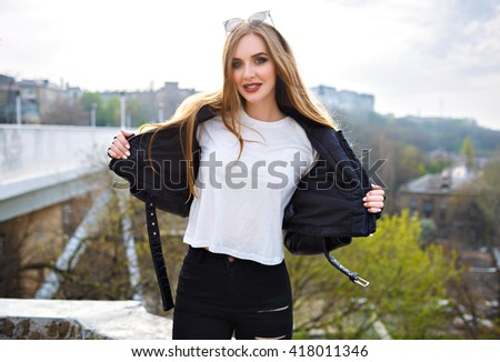 Fashion outdoor portrait of stunning blonde woman take of her leather jacket, urban bridge city background, bright make up and long hairs, street style.  - stock photo