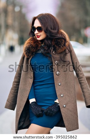 fashion Outdoors Sexy glamor young woman with chic long dark hair beautiful young brunette girl wearing stylish sunglasses, trendy green dress, luxurious fur coats and gloves, fashion makeup posing in - stock photo