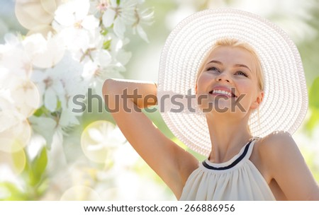 fashion, people and summer holidays concept - beautiful woman in hat and dress over green blooming garden background - stock photo