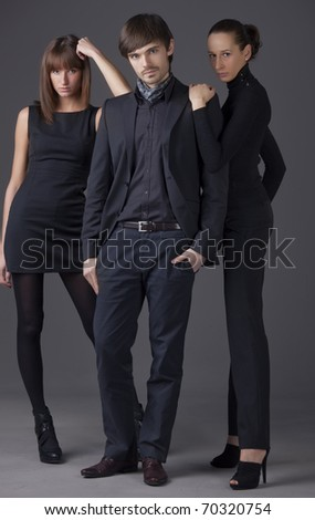 fashion people - man and two women in elegant dresses - stock photo