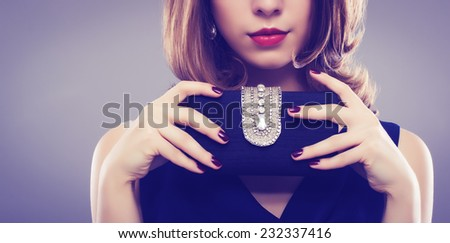 Fashion photo. Beautiful young woman with a black clutch in hand.