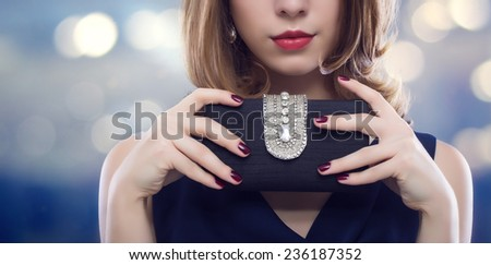 Fashion photo. Beautiful young woman with a black clutch in hand. - stock photo